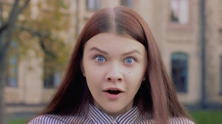 expressed : Emotional video-portrait of a surprised beautiful young girl. Blue-eyed brown-haired lady abruptly expresses surprise and looks into the frame