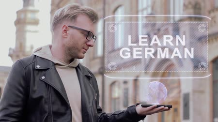 dicionário : Smart young man with glasses shows a conceptual hologram Learn German. Student in casual clothes with future technology mobile screen on university background