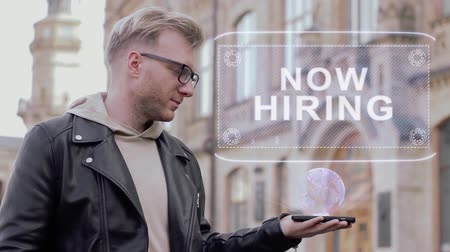 bezrobotny : Smart young man with glasses shows a conceptual hologram Now Hiring. Student in casual clothes with future technology mobile screen on university background