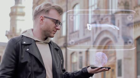 optyk : Smart young man with glasses shows a conceptual hologram eyeglasses. Student in casual clothes with future technology mobile screen on university background