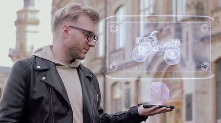 quad bike : Smart young man with glasses shows a conceptual hologram quad bike. Student in casual clothes with future technology mobile screen on university background