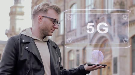 standardization : Smart young man with glasses shows a conceptual hologram 5G. Student in casual clothes with future technology mobile screen on university background Stock Footage