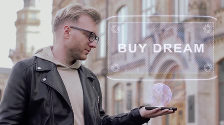árverés : Smart young man with glasses shows a conceptual hologram Buy dream. Student in casual clothes with future technology mobile screen on university background