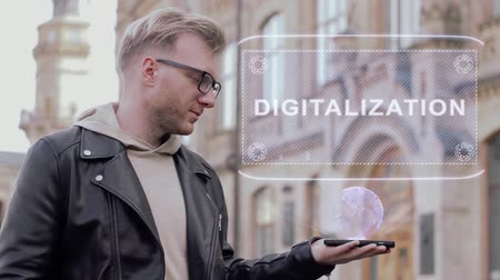 inteligentní : Smart young man with glasses shows a conceptual hologram Digitalization. Student in casual clothes with future technology mobile screen on university background