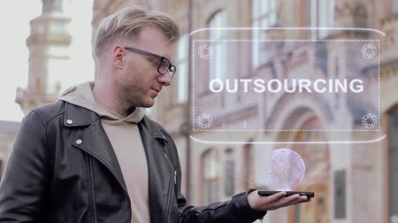 competence : Smart young man with glasses shows a conceptual hologram Outsourcing. Student in casual clothes with future technology mobile screen on university background