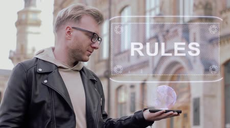 regra : Smart young man with glasses shows a conceptual hologram Rules. Student in casual clothes with future technology mobile screen on university background