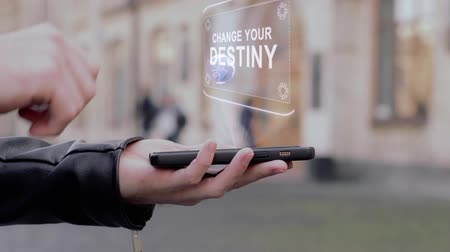 destiny : Male hands show on smartphone conceptual HUD hologram Change your destiny. Man with the future technology mobile holographic screen on blurred background of the university Stock Footage