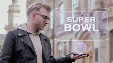 playoff : Smart young man with glasses shows a conceptual hologram Super bowl. Student in casual clothes with future technology mobile screen on university background