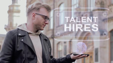 прокат : Smart young man with glasses shows a conceptual hologram Talent hires. Student in casual clothes with future technology mobile screen on university background