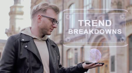 uygulanması : Smart young man with glasses shows a conceptual hologram Trend breakdowns. Student in casual clothes with future technology mobile screen on university background
