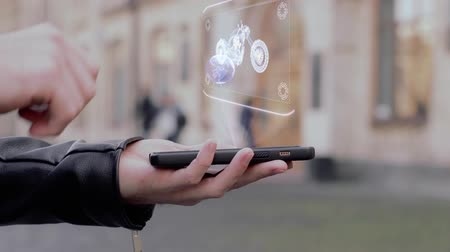 モト : Male hands show on smartphone conceptual HUD hologram road bike. Man with the future technology mobile holographic screen on blurred background of the university