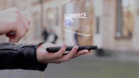 бумажник : Male hands show on smartphone conceptual HUD hologram E-commerce. Man with the future technology mobile holographic screen on blurred background of the university