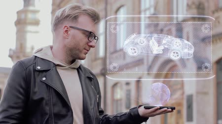 projeksiyon : Smart young man with glasses shows a conceptual hologram chassis. Student in casual clothes with future technology mobile screen on university background Stok Video