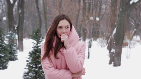 zmrazit : A beautiful woman tries to warm her frozen hands with her breath on a winter outdoors. Girl with frosty breath freezes while waiting for someone in the winter park