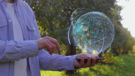 improve : Unrecognizable man shows conceptual hologram with text Automation. Farmer on the background of the apple orchard in casual clothes with the technology of the future mobile screen