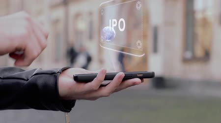 initial : Male hands show on smartphone conceptual HUD hologram IPO. Man with the future technology mobile holographic screen on blurred background of the university