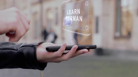немецкий : Male hands show on smartphone conceptual HUD hologram Learn German. Man with the future technology mobile holographic screen on blurred background of the university