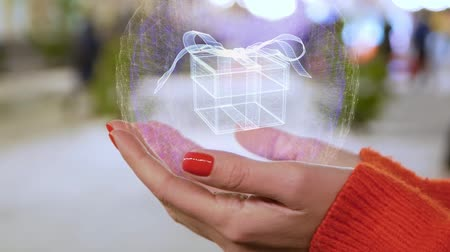 wrapped up : Female hands holding a conceptual hologram with gift box. Woman with red nails and sweater with future holographic technology on a blurred background of the street Stock Footage