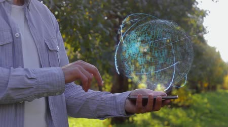 назначение : Unrecognizable man shows conceptual hologram with text Leader. Farmer on the background of the apple orchard in casual clothes with the technology of the future mobile screen Стоковые видеозаписи
