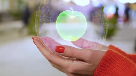 apple sign : Female hands holding a conceptual hologram with apple. Woman with red nails and sweater with future holographic technology on a blurred background of the street Stock Footage