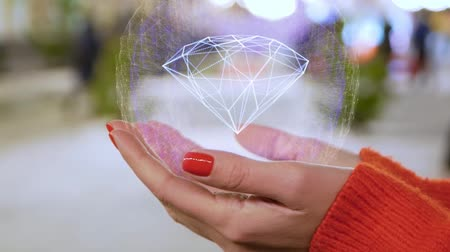 подарок : Female hands holding a conceptual hologram with diamond. Woman with red nails and sweater with future holographic technology on a blurred background of the street