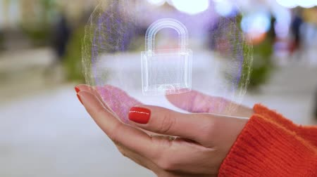 kłódka : Female hands holding a conceptual hologram with padlock. Woman with red nails and sweater with future holographic technology on a blurred background of the street