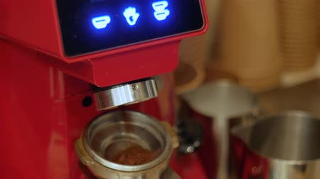 suporte : An electric coffee grinder grinds freshly roasted coffee beans into a filter holder. Barista girl is holding portafilter with ground coffee. Making an espresso process Stock Footage