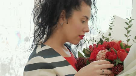 obrigado : Beautiful curly woman with a gorgeous bouquet near the window. An attractive girl with a lovely smile enjoys the scent of flowers. Business Lady gently touches delicate roses