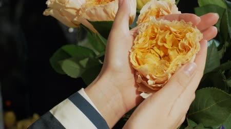 charisma : Female hands form a bouquet with yellow and orange roses. The girl enjoys the beauty of flowers. Business woman gently touches delicate roses