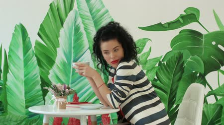kafeterya : A young, beautiful woman in a striped suit holding a cup of coffee on a background of painted green leaves. Curly girl enjoying coffee in a cafe Stok Video