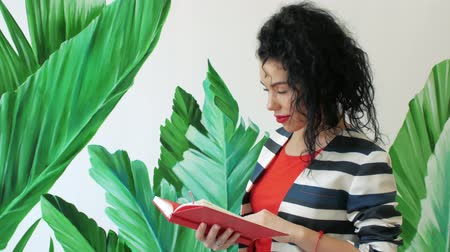 メモ帳 : A young, beautiful curly woman in a striped suit looks through the pages in a notebook on the background of painted green leaves with copy space. Girl reading a book near the wall 動画素材