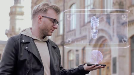descarga : Smart young man with glasses shows a conceptual hologram gas discharge bulb. Student in casual clothes with future technology mobile screen on university background Vídeos