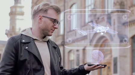holographic : Smart young man with glasses shows a conceptual hologram propeller plane. Student in casual clothes with future technology mobile screen on university background Stock Footage
