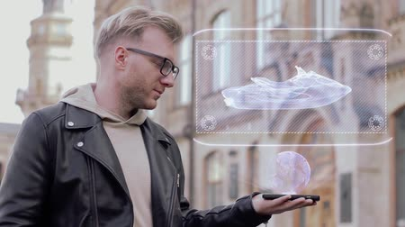 highspeed : Smart young man with glasses shows a conceptual hologram water scooter. Student in casual clothes with future technology mobile screen on university background Stock Footage