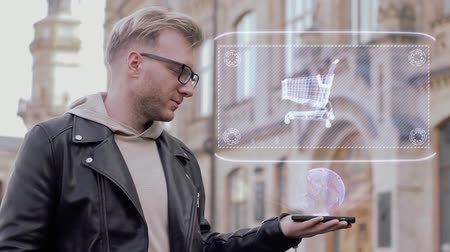 troli : Smart young man with glasses shows a conceptual hologram shopping cart. Student in casual clothes with future technology mobile screen on university background Stock mozgókép