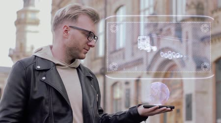tir : Smart young man with glasses shows a conceptual hologram TIR Truck. Student in casual clothes with future technology mobile screen on university background