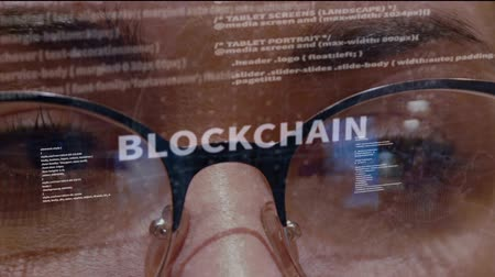 estratégico : Blockchain text on the background of female software developer. Eyes of woman with glasses are looking at programming network code space abstract technologies connecting global data network