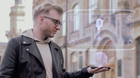 голос : Smart young man with glasses shows a conceptual hologram rotating vocal microphone. Student in casual clothes with future technology mobile screen on university background Стоковые видеозаписи