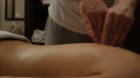 masażysta : Man Manual therapist massaging a young woman lying on a massage table, pushing on the back. Professional spa massage of female spine and back treatment, close up