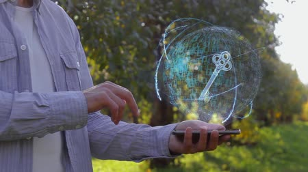 tuşları : Unrecognizable man shows conceptual hologram with key. Farmer on the background of the apple orchard in casual clothes with the technology of the future mobile screen Stok Video