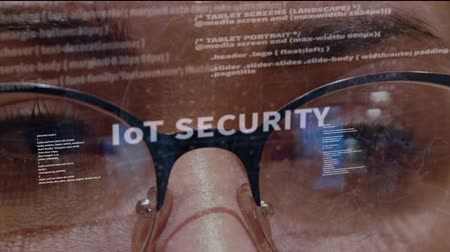 hozzáférés : IoT SECURITY text on the background of female software developer. Eyes of woman with glasses are looking at programming network code space abstract technologies connecting global data network