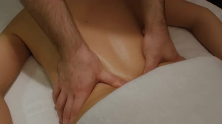 restorative : Relaxing massage of the female back and lower back. Male hands doing professional restorative massage to a woman on a massage table Stock Footage