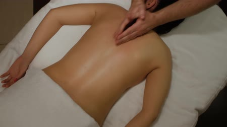 restorative : Therapeutic massage with fists and wrists of the female back. Male hands doing professional restorative massage to a woman on a massage table