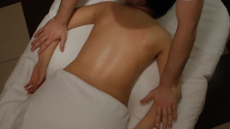 terapi : Massage of womens shoulders and arms. Male hands doing professional massage to a woman on a massage table