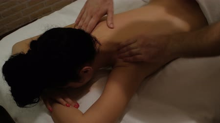 restorative : Therapeutic massage of the female shoulders and neck. Male hands doing professional massage to a woman on a massage table