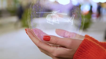 ротор : Female hands holding a conceptual hologram with helicopter. Woman with red nails and sweater with future holographic technology on a blurred background of the street
