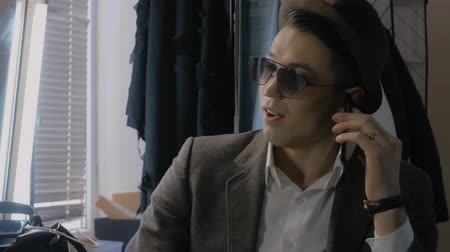 dressing room : A young man in a hat is talking on the phone in the dressing room and looks out the window. Actor calls during a break Stock Footage