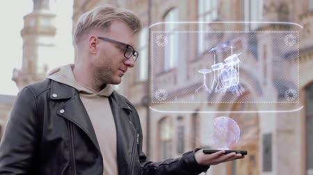 банда : Smart young man with glasses shows a conceptual hologram drum set. Student in casual clothes with future technology mobile screen on university background