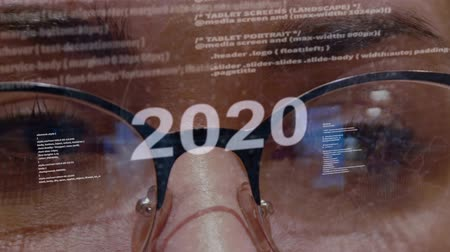 talep : 2020 text on the background of female software developer. Eyes of woman with glasses are looking at programming network code space abstract technologies connecting global data network Stok Video