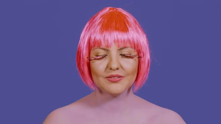 vokal : Stylish young woman back vocalist sings la la la and looks directly into the frame on a blue background. A girl with a bright make-up and red-pink hair performs vocals emotionally Stok Video